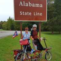 Cyclists riding a tandem bike at the Tennessee - Alabama State Line