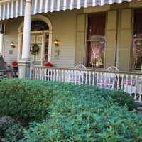 The front porch at the 1893 Queen Ann Victorian Main House offers a shady spot to sit and admire the beautiful gardens.