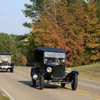 Antique cars driving towards Tupelo on a fall day.