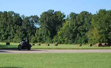 Motorcycles riding past Bear Creek Mound.